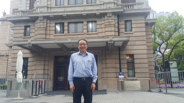 Charles Liu poses in front of the Shanghai History Museum. The site formerly housed a library, which he credits for helping him enter university and altering the course of his life. Credit: Jennifer Pak/Marketplace