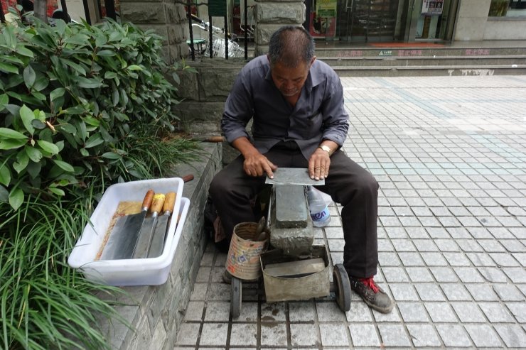 An elderly man from eastern Anhui province sharpens knives outside a supermarket in Shanghai. Credit: Charles Zhang/Marketplace