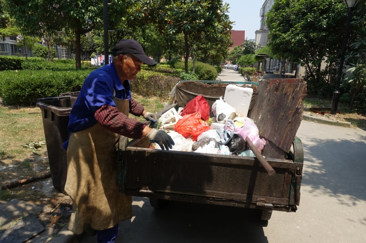 Li Xin'an collects garbage in a residential compound in Shanghai and earns at least three times more than what he could get farming in his village in central Henan province. Credit: Charles Zhang/Marketplace