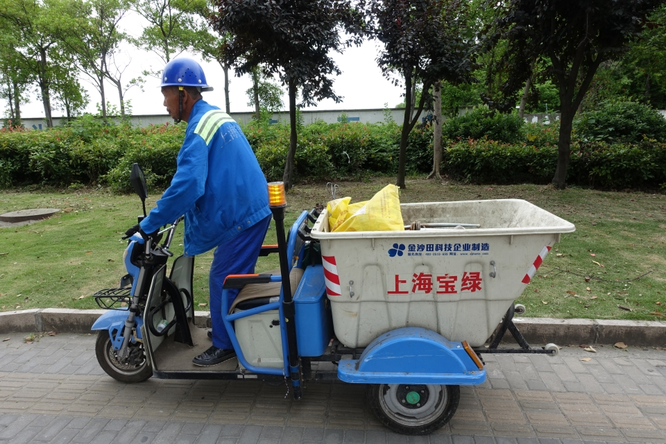 An elderly man picking trash along Shanghai's streets for $12 a day.