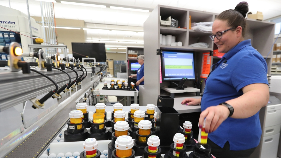 A pharmacy technician prepares prescriptions for packaging and shipping after being filled on an automated line at the central pharmacy of Intermountain Heathcare in 2018 in Midvale, Utah.