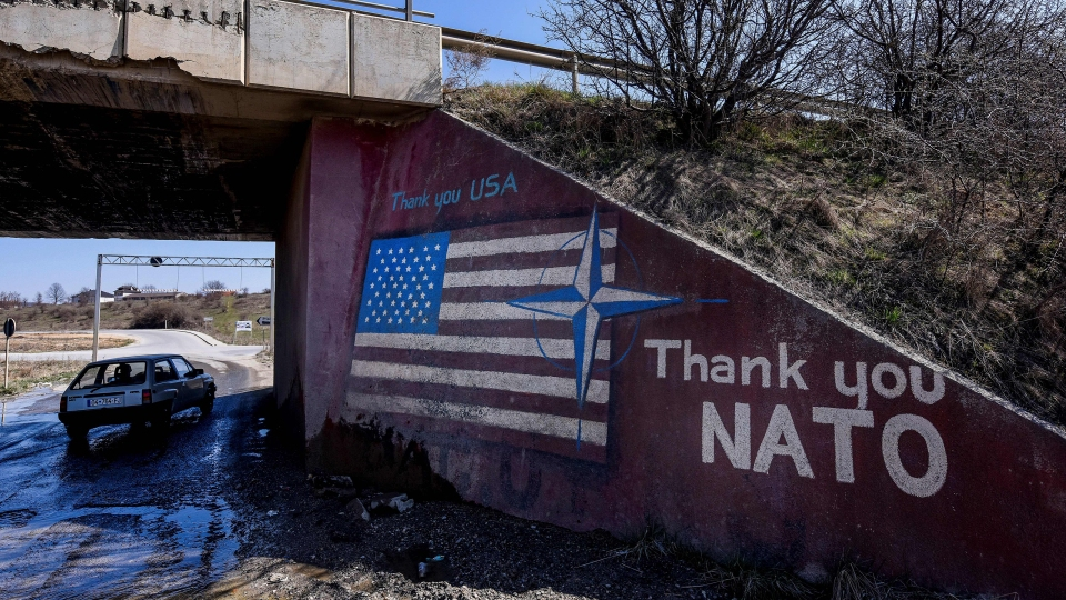 "A car drives past graffiti reading ""Thank you NATO"" and featuring the U.S. flag near the village of Stagovo, Kosovo, on March 24."
