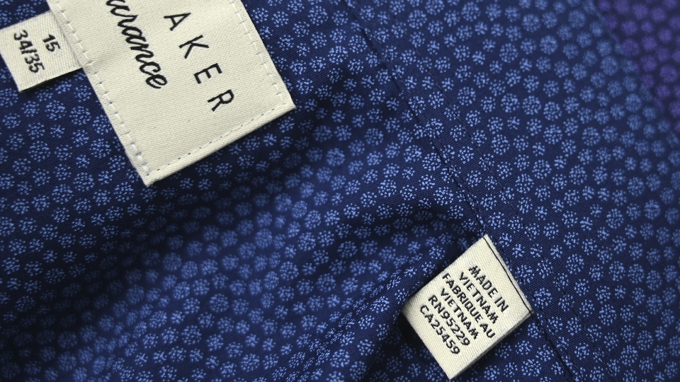 """This photograph taken on May 24, 2019 shows a Ted Baker brand men's shirt labeled """"Made in Vietnam"""" in a factory in Hanoi."""