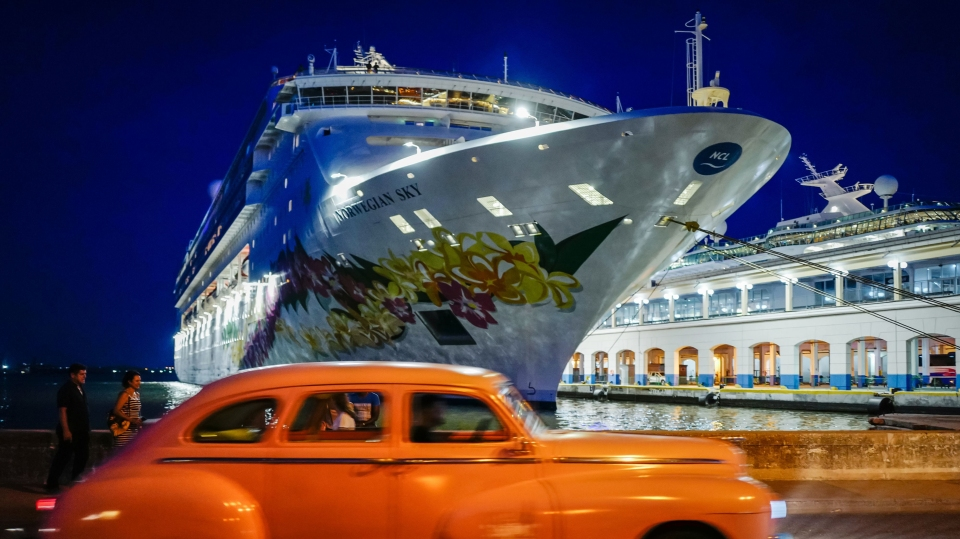 An old American car passes in front of a cruise docked at Havana's Harbour, on June 5, 2019.