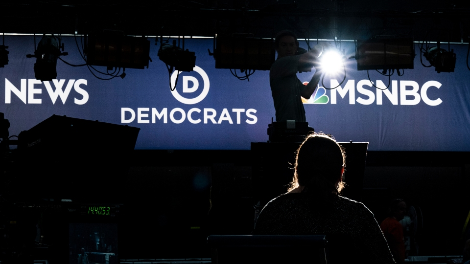 Workers prepare a set for the Democratic primary debate taking place in Miami on June 26 and 27.