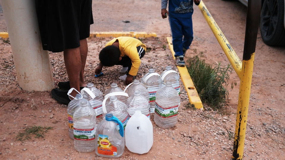 Children play as a woman, a member of the Navajo Nation, fills bottles of water at a public tap on June 05, 2019 in Thoreau, New Mexico.