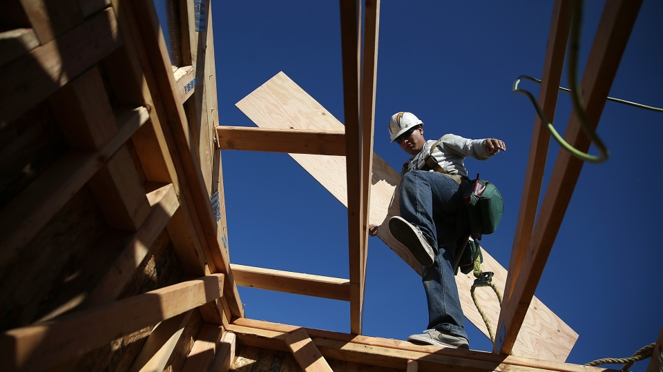 A construction worker carries lumber as he builds a new home in Petaluma, California, in 2015.