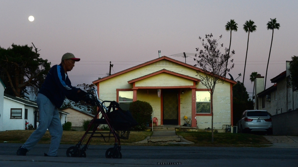 An elderly man pushes his walker beneath an almost full moon during early evening in Monterey Park, Los Angeles County,
