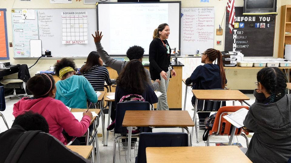 A science teacher works with students in a high school in Homestead, Florida, in 2017.