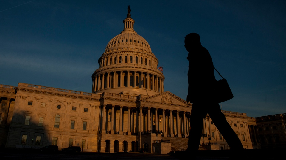 A person walks outside the Capitol Building as the sun rises over Washington, D.C.