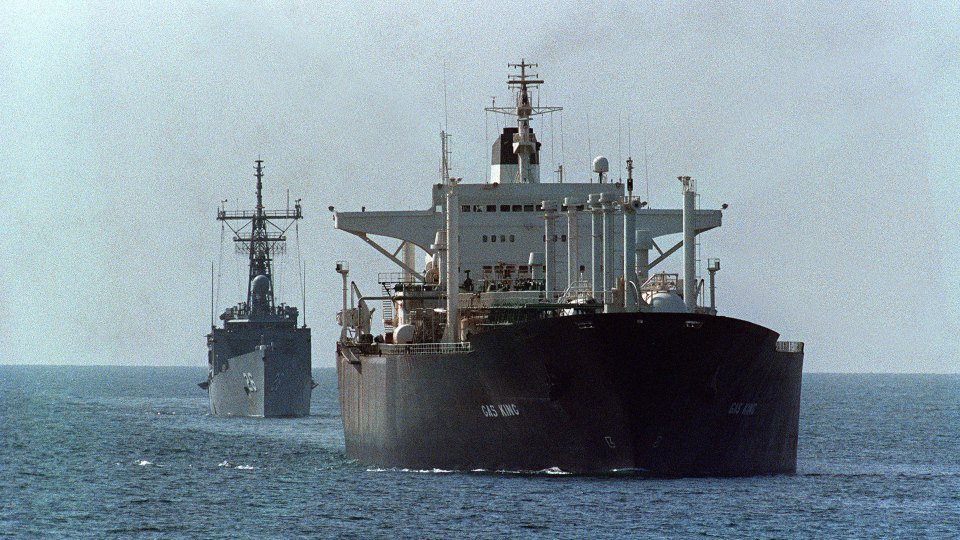 An oil tanker is protected by the U.S. guided missile frigate USS Gallery in the Strait of Hormuz in 1988. In a tweet Monday, President Donald Trump questioned the United States' decadeslong protection of the strait.
