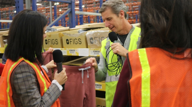 FIGS Co-CEO/Co-Founder Trina Spear shows Marketplace's Kai Ryssdal a set of FIGS scrubs.