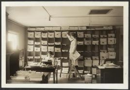 In an archival photo, two women work in a newsroom. One stands on a ladder in front of a wall of cubbyholes filled with stacks of papers. The other writes a typewriter as the sun streams in from a window on the left on the image.