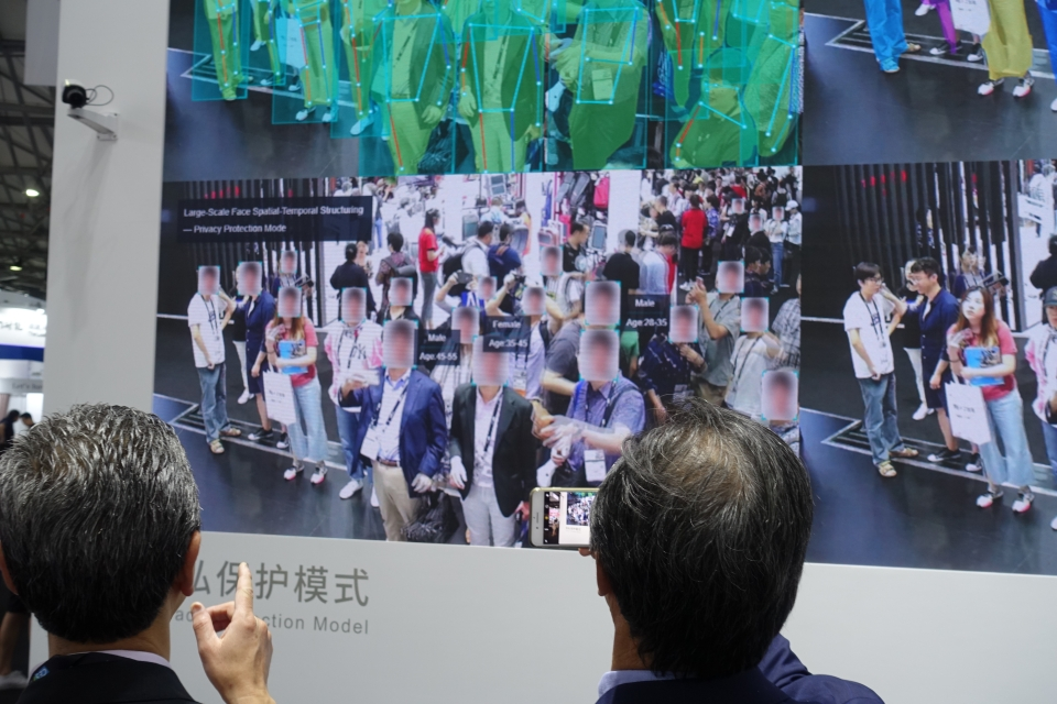 A Chinese tech firm showcases its facial recognition security equipment at the Consumer Electronics Show in Shanghai June 2019. The success of these companies is partly built on the backs of workers putting in extreme overtime.