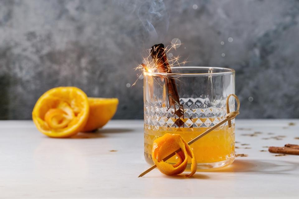 Glass of Scotch Whiskey orange juice alcohol cocktail with swirled orange peel and smoking cinnamon sticks. (Photo by: Natasha Breen/REDACO/Universal Images Group via Getty Images)
