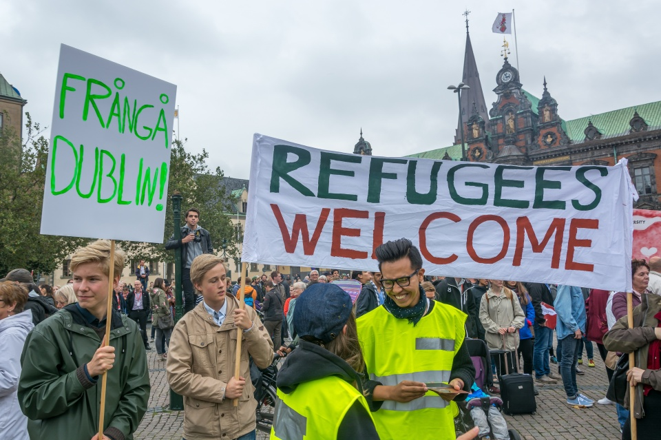 People hold banners welcoming refugees in Malmö, Sweden.