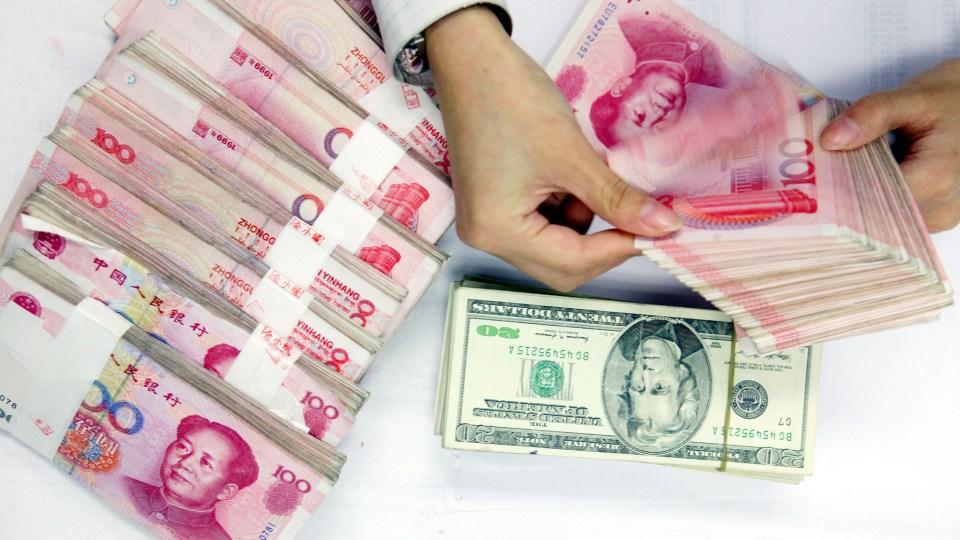 A clerk counts stacks of Chinese yuan and U.S. dollars at a bank in Shanghai, China.