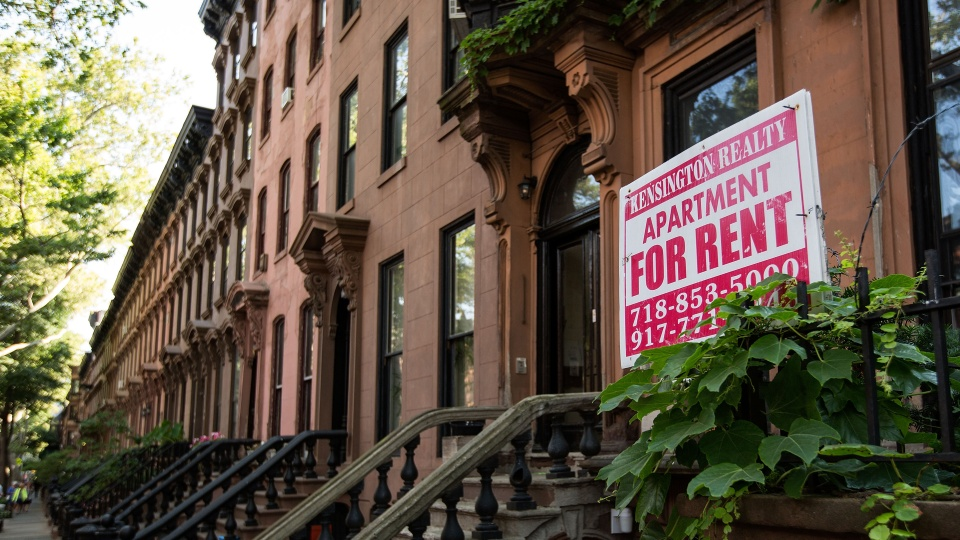 A sign advertises an apartment for rent along a row of brownstone townhouses in New York City.
