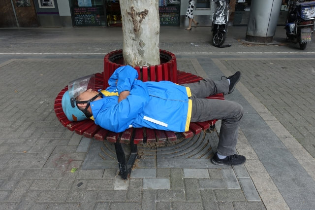 A food delivery worker in Shanghai takes a rest. Chinese workers on average work 12 hours more per week than their American counterparts according to U.S. and China government statistics for May. Photo credit: Charles Zhang/Marketplace