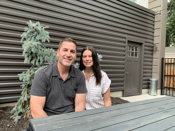 Nate and Stacie sit in the courtyard between the ADU and the house, which became a neighborhood gathering space.