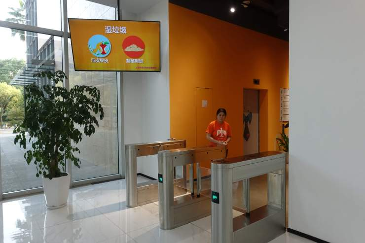 """A screen at the entrance of E-commerce firm Baiqiu reminds staff what goes into """"wet"""" garbage bins. Credit: Charles Zhang/Marketplace"""