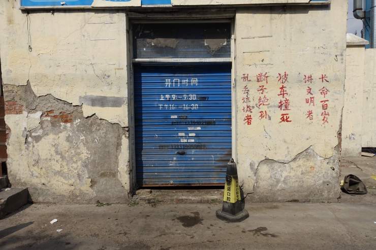 """A poem next to the entrance of a waste sorting station reads:  """"Those who litter, have no descendants, get run over by a car. Those who are civilized, live for a hundred years."""" Credit: Charles Zhang/Marketplace v"""