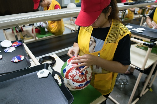 Deng Lijuan assembles a soccer ball. It's the only part of the production that the Shuoke factory has not automated yet. (Shanghai 808 Studio)