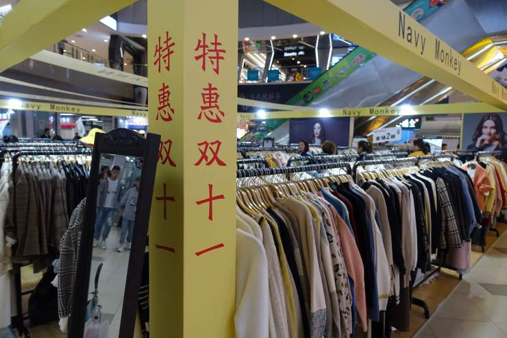 A sign on a Shanghai clothing shop with a less splashy sign advertising discounts for Singles Day. More offline shops are participating in what has widely been seen as an e-commerce event. (Charles Zhang/Marketplace)