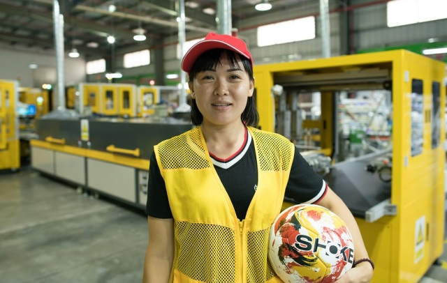 Ding Ling supervises soccer ball production at the Shuoke factory. She is not required to put in a lot of overtime like she had in other factories. (Shanghai 808 Studio)