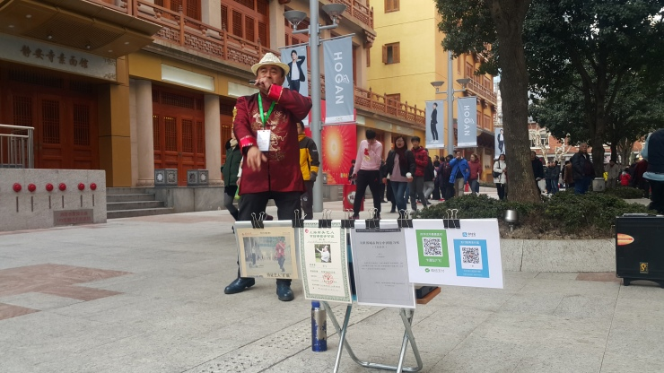 A street performer displays QR codes for passersby to scan and tip through mobile payment apps WeChat and Alipay. (Jennifer Pak/Marketplace)