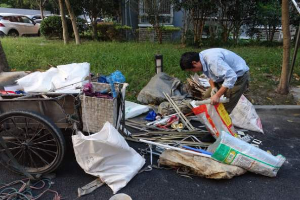 A man sorts through recyclables in Shanghai. Low-paid workers like him will not likely be able to receive a pension by the time he retires. (Credit: Charles Zhang/Marketplace)