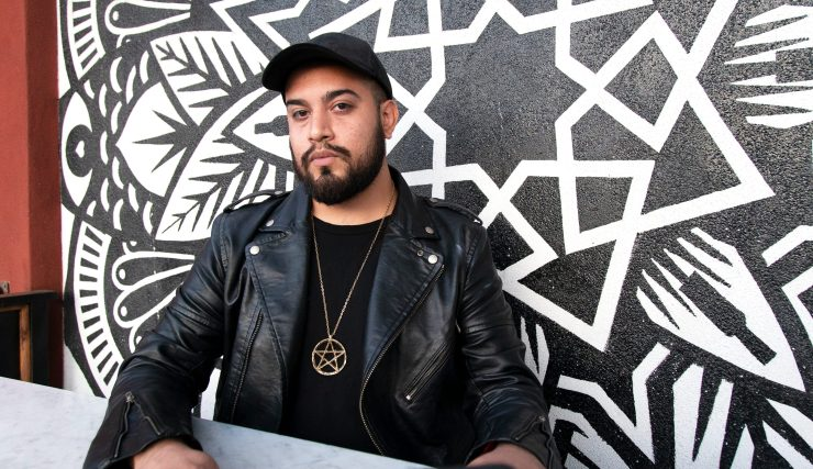 Michael Cardenas sits in front of a black and white mural at a San Diego cafe