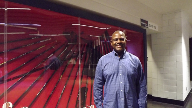 DC Elections Chairman Michael Bennett stands in front of a display of hockey sticks at Capital One Arena.