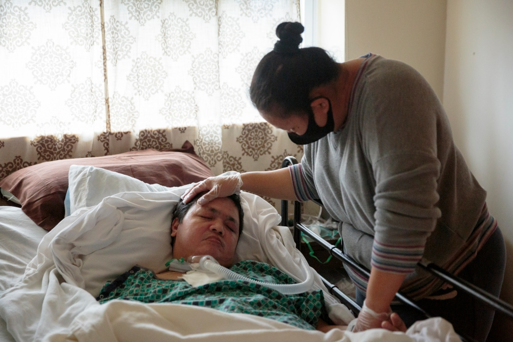 Alberto Castillo, an Amazon worker, lies in bed after falling severely ill from the coronavirus. His wife Ann Castillo, wearing a mask and gloves, stands over him.