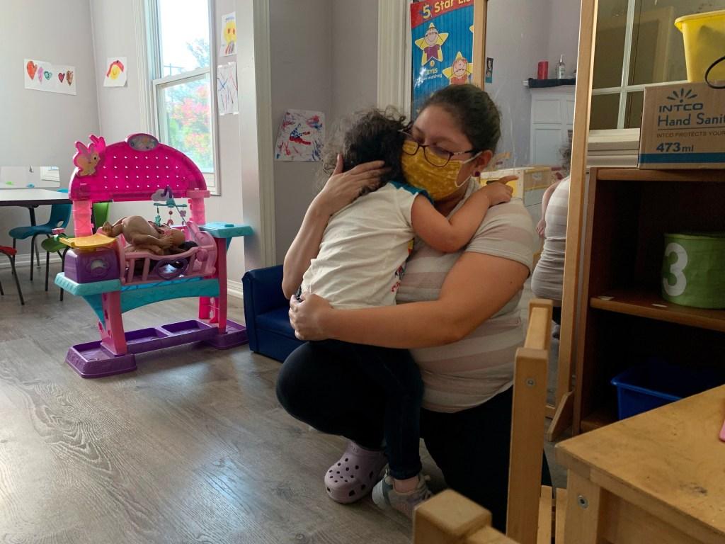 Andrea Hernandez hugs a child at Hernandez's daycare.