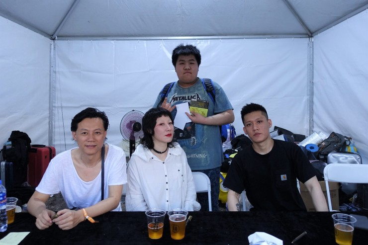 A fan (center back)poses with punk band Subs after getting an autograph. He spent $120 on a three-day ticket for the music festival, which he said was a tad expensive. (Charles Zhang/Marketplace)