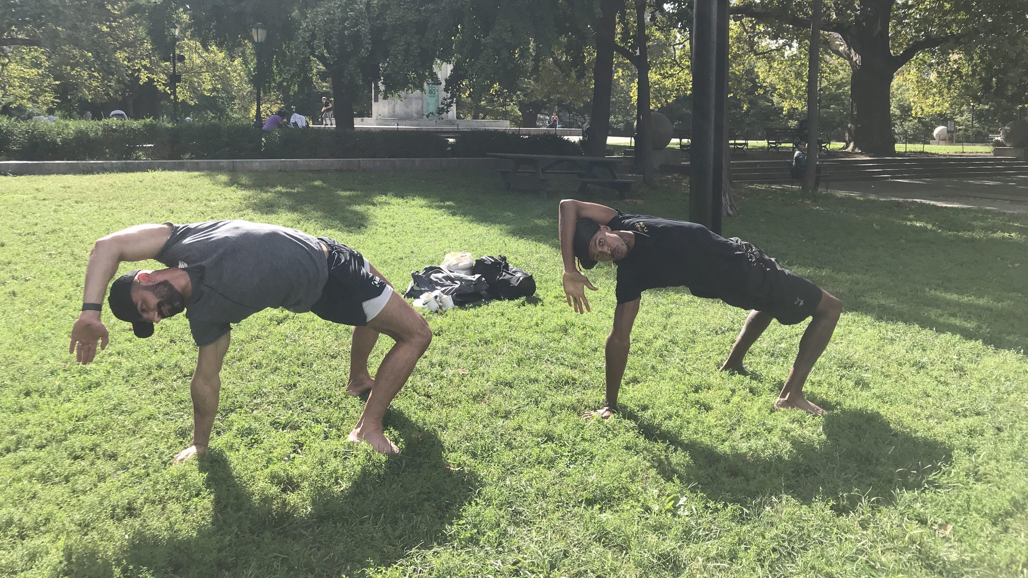 Personal trainers pose in semi-bridge position in Fort Greene park.