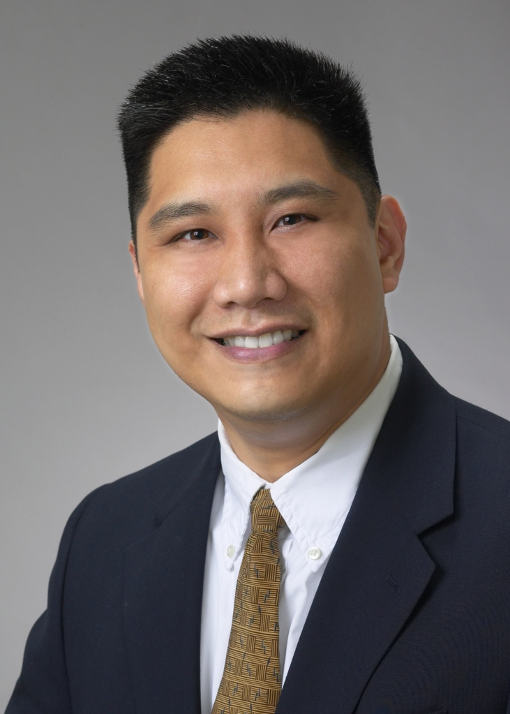 Ramon Llamas smiles for his headshot wearing a dark blazer and brown tie.