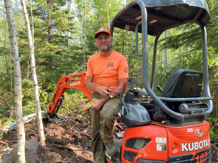 Blu Tenbrink of Rock Solid Trail Contracting takes a break on his excavator while building a new trail in the Split Rock Wilds trail system in Lake County on Aug 9